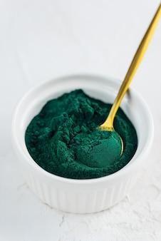 Sluit omhoog van groen spirulinapoeder in een kom