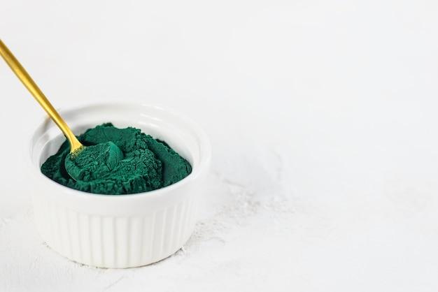Sluit omhoog van groen spirulinapoeder in een lepel en een kom