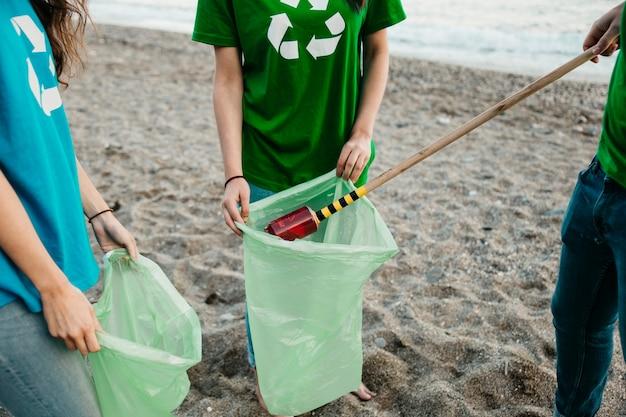 Sluit omhoog van groep vrijwilligers verzamelend afval bij het strand