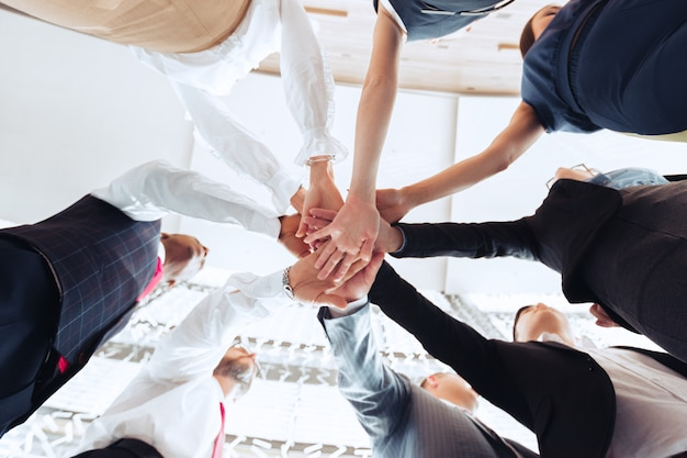 Sluit omhoog van groep zakenlui die hun handen bovenop elkaar zetten