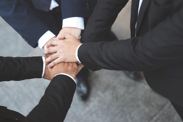 Sluit omhoog van groepsmensen van zakenlieden die samen hun handen verenigen