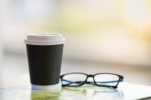 Sluit omhoog van haal document kop van hete koffie met leesbril op wereldkaart weg