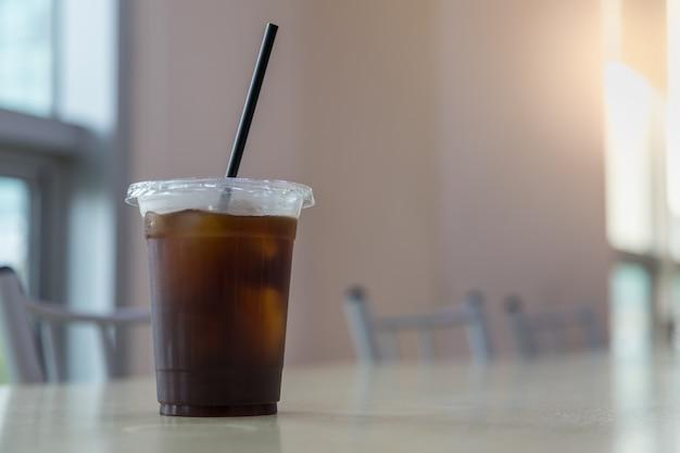 Sluit omhoog van haal plastic kop van bevroren zwarte koffie (americano) op lijst met exemplaarsapce weg.