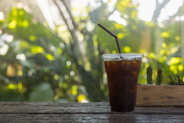 Sluit omhoog van haal plastic kop van bevroren zwarte koffie (americano) weg onder zonlicht op houten lijst in tuin met de groene achtergrond van de bladaard.