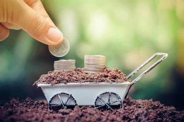 Sluit omhoog van hand die muntstukken in stapel muntstukken zetten groeit op wielkruiwagen voor bedrijfsinvesteringen of besparingsconcept