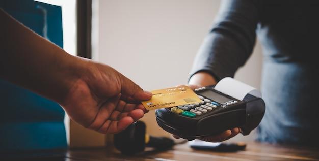 Sluit omhoog van hand gebruikend creditcard om te betalen door de creditcard naar het personeel bij de creditcard veegmachine te verzenden. online betaling