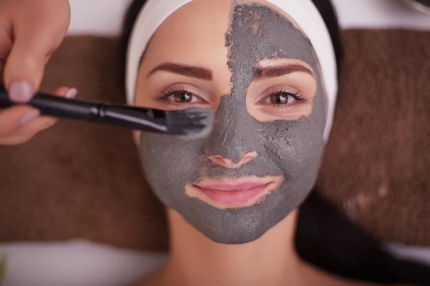 Sluit omhoog van hand gezichtsmasker toepassen op vrouwengezicht bij schoonheidssalon