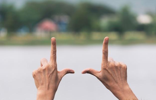 Sluit omhoog van handen die frame gebaar maken. sluit omhoog van vrouwenhanden makend kadergebaar met zonsondergang.