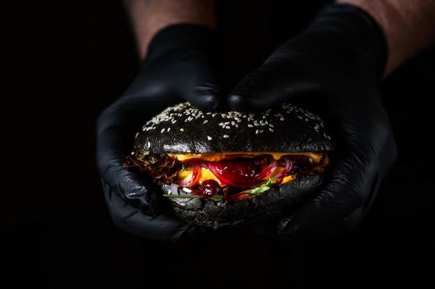 Sluit omhoog van handen houdend zwarte sappige hamburger met amerikaanse veenbessaus op donkere oppervlakte