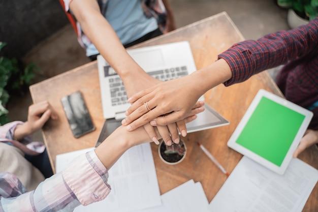 Sluit omhoog van handen jonge aziatische studenten die in een koffie samenkomen die high five doen