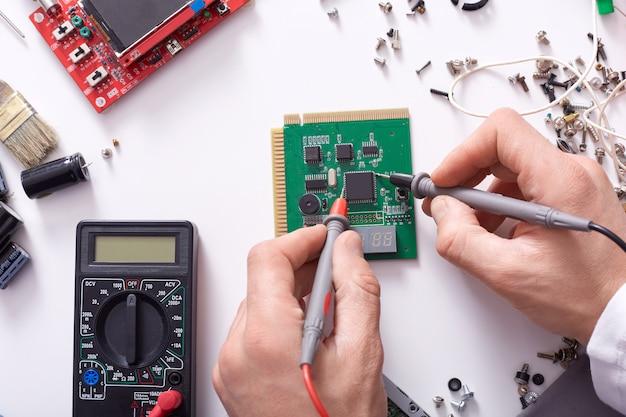 Sluit omhoog van handen van de mens die computerdeel met soldeerbout herstellen, hersteller het werken