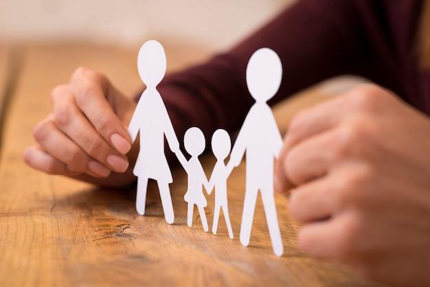 Sluit omhoog van handen van een man en vrouwenholding document kettingfamilie. jong koppel besluit over leven na huwelijk. close-up beeld van witboek gesneden familie bedrijf tussen handen.