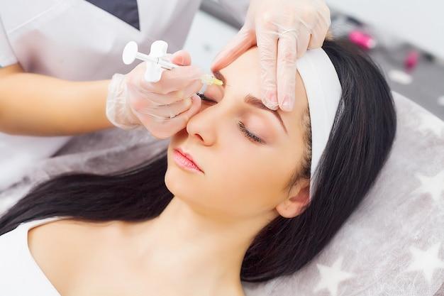 Sluit omhoog van handen van schoonheidsspecialist die botox injectie in vrouwelijke lippen maken