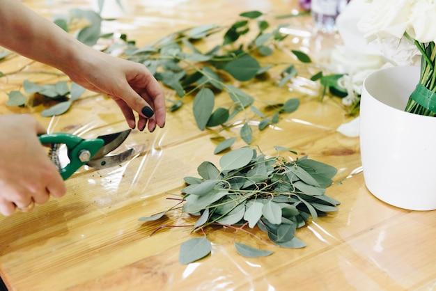 Sluit omhoog van handen van vrouwelijke kaukasische bloemist aangezien zij werkt