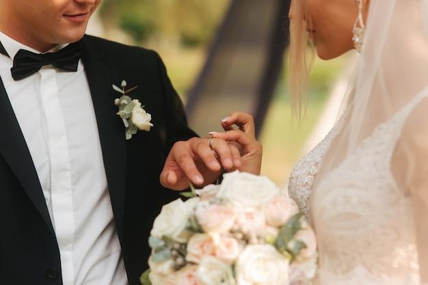 Sluit omhoog van handenbruidegom en bruid die een ring dragen
