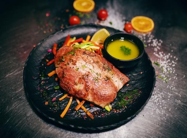 Sluit omhoog van heerlijk tonijnlapje vlees op knapperige groenten. op een bordje kom soep ook.