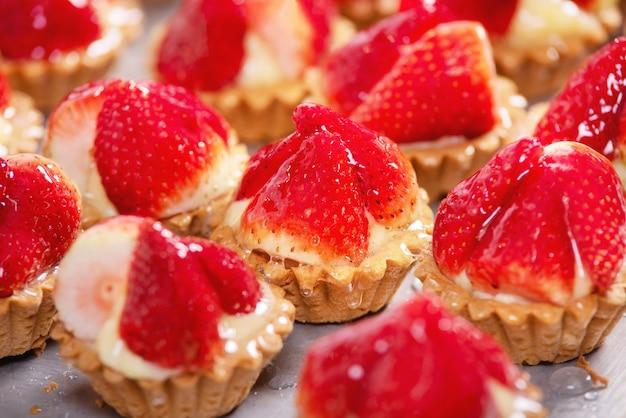 Sluit omhoog van heerlijke tartlets met verse aardbeien en vanilleroom.