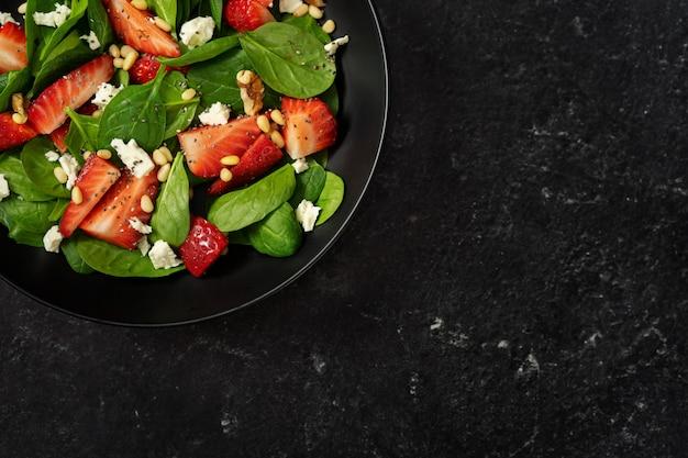 Sluit omhoog van heldere aardbeisalade met spinazie op zwarte achtergrond
