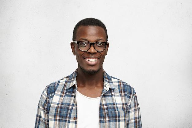Sluit omhoog van het aantrekkelijke slim uitziende het glimlachen donkerhuidige mannelijke model stellen