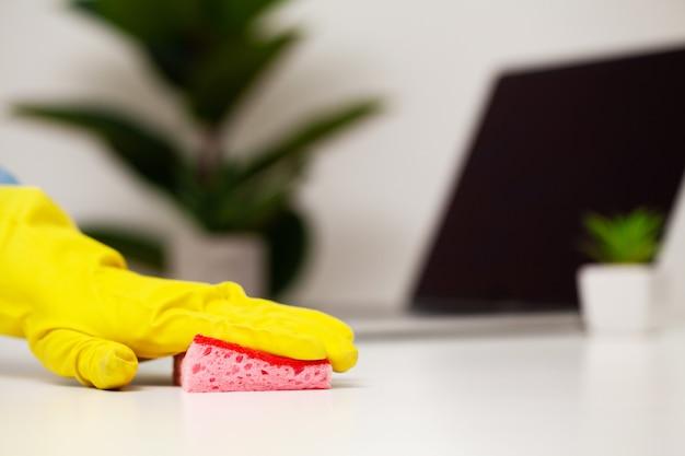 Sluit omhoog van het afvegende stof van de arbeidershand in bureau in gele handschoenen
