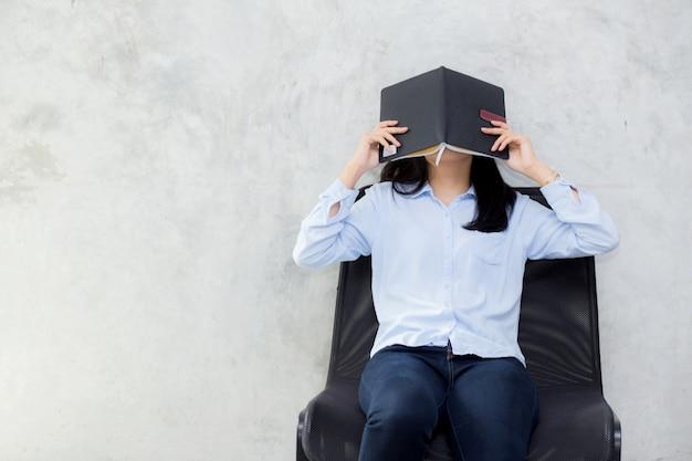 Sluit omhoog van het aziatische boek van de vrouwenlezing en verbergend gezicht op cementachtergrond.
