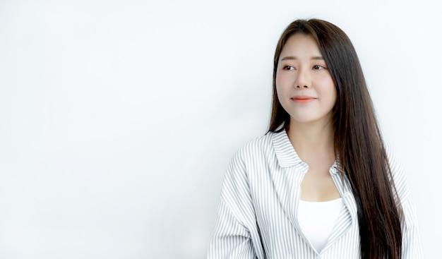 Sluit omhoog van het aziatische vrouwenportret met lang haar dat recht vooruit kijkt.