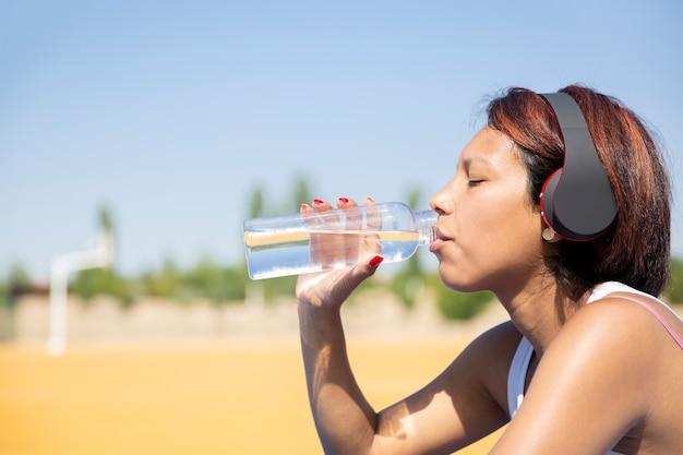 Sluit omhoog van het drinkwater van een vrouw in de open lucht