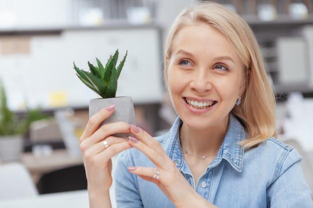 Sluit omhoog van het gelukkige mooie vrouw lachen, houdend weinig aloë in een pot