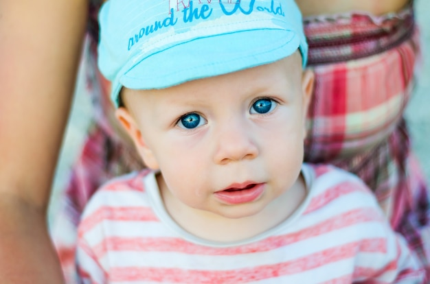 Sluit omhoog van het gezicht van de babyjongen met blauwe ogen met open mond en blauw glb. kind en kinderen emoties concept.
