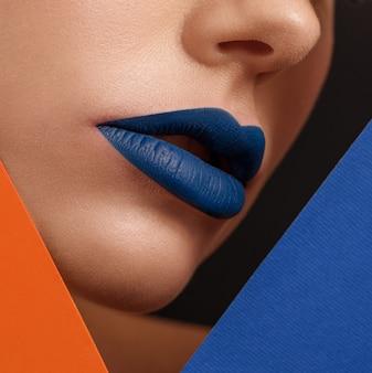 Sluit omhoog van het gezicht van de vrouw met lippen die met donkerblauwe lippenstift worden behandeld.