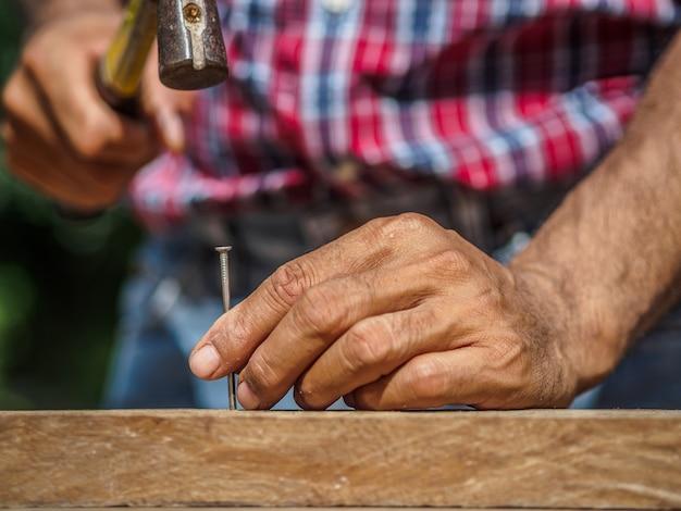 Sluit omhoog van het hameren van een spijker in houten raad