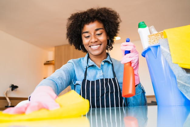 Sluit omhoog van het jonge afrovrouw schoonmaken bij nieuw huis. huishoudelijk en schoonmaakconcept.