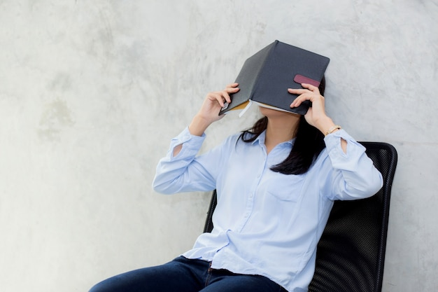 Sluit omhoog van het jonge aziatische boek van de vrouwenlezing en verbergend gezicht op cementachtergrond