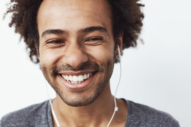 Sluit omhoog van het jonge gelukkige afrikaanse mens glimlachen die lachen.