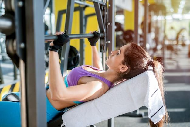 Sluit omhoog van het jonge geschikte gewicht van de meisjesholding in haar wapens. gym training in lichte sportschool.