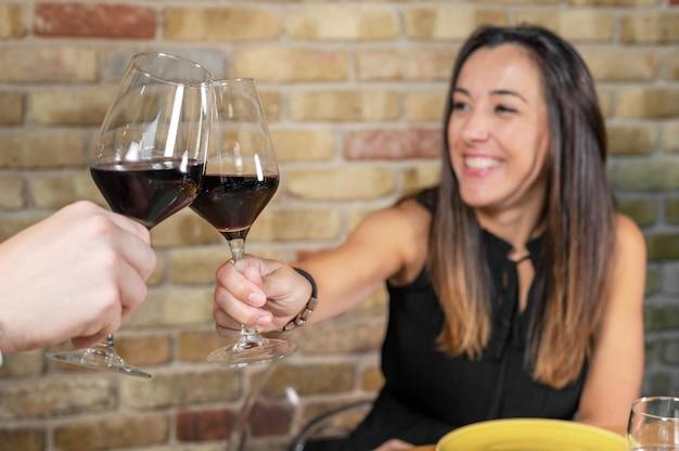 Sluit omhoog van het jonge paar roosteren met glazen rode wijn bij restaurant