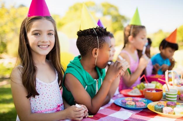 Sluit omhoog van het leuke meisje glimlachen voor andere kinderen tijdens een verjaardagspartij