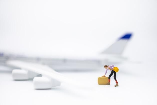 Sluit omhoog van het miniatuurcijfer van de vrouwenreiziger met bagage zich op wit met ministuk speelgoed vliegtuigmodel bevinden.