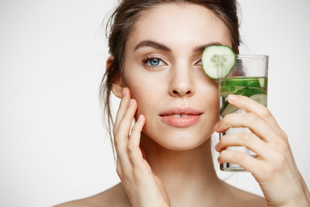 Sluit omhoog van het mooie naakte meisje glimlachen bekijkend het glas van de cameraholding water met komkommerplakken over witte achtergrond. gezonde voeding. schoonheid en huidverzorging.