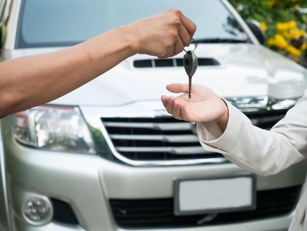 Sluit omhoog van het overhandigen van de sleutels voor een auto aan een jonge zakenman. autorijden, reizen, auto huurauto, veiligheidsverzekering
