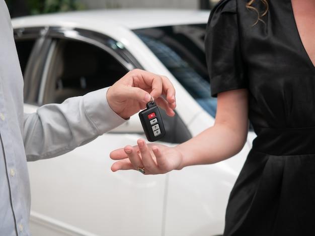 Sluit omhoog van het overhandigen van de sleutels voor een auto aan een jonge zakenman.