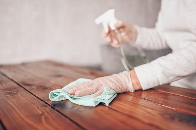 Sluit omhoog van het schoonmaken van houten huislijst, reinigend keukentafeloppervlak met desinfecterende antibacteriële nevelfles, wasoppervlakken met handdoek en handschoenen.