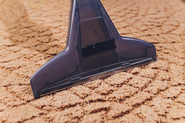 Sluit omhoog van het schoonmakende tapijt van de stofzuigerpijp thuis.