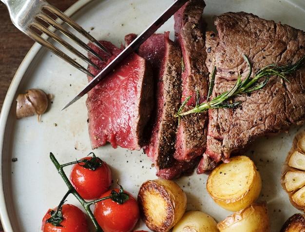 Sluit omhoog van het snijden van een het idee van het de fotografie recept van het filetlapje vleesvoedsel