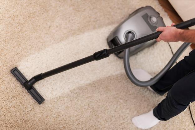 Sluit omhoog van het stofzuigen van een tapijt