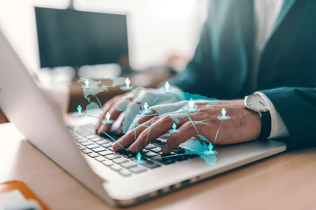 Sluit omhoog van het succesvolle zakenman typen op laptop terwijl het zitten in bureau.