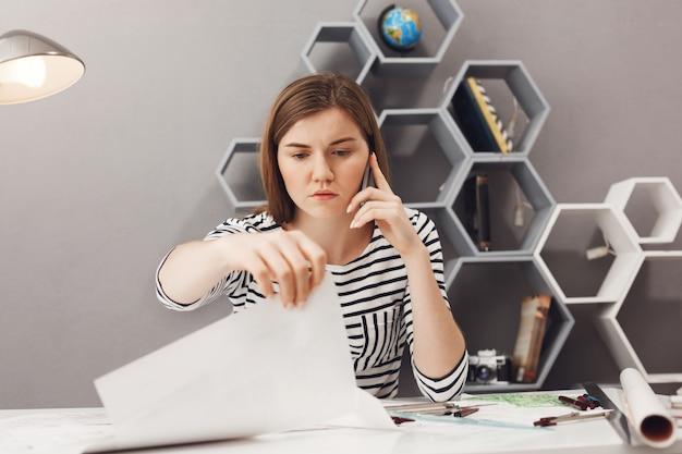Sluit omhoog van het verstoorde jonge knappe europese freelance architect spreken op telefoon met ongelukkige uitdrukking, proberend o probleem met teamleider op te lossen, kijkend door documenten.