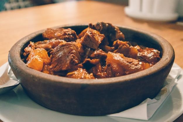 Sluit omhoog van hete die rundvleeshutspot in kleikom wordt gediend.