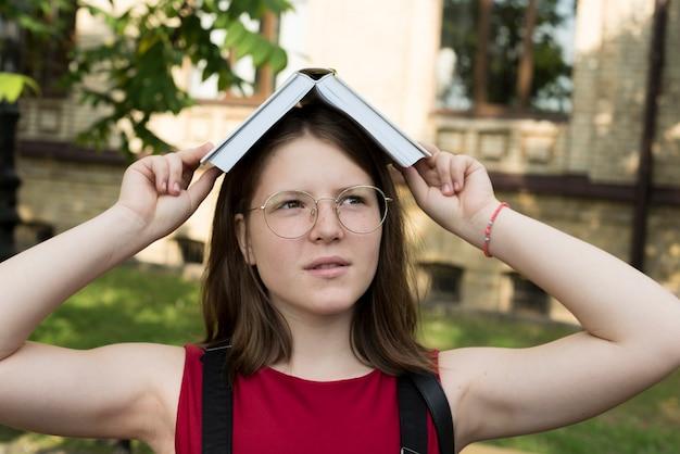 Sluit omhoog van highschool gil houdend open boek op hoofd