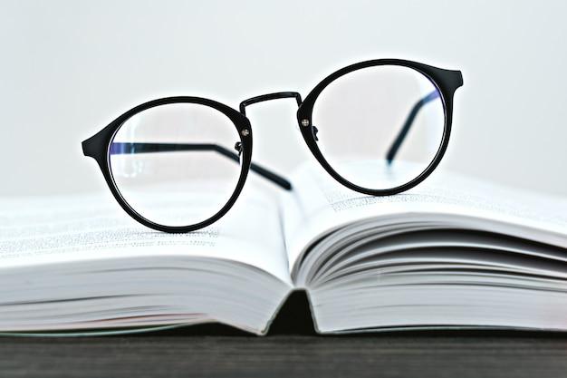 Sluit omhoog van hipsterglazen voor lezing op een open boek